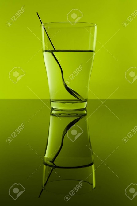 20391403-glass-of-water-with-spoon-in-green-background-with-reflection--Stock-Photo.jpg